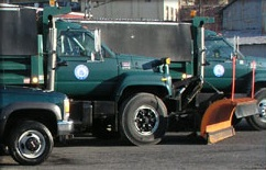 2 green snow plow trucks